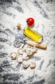 Ravioli mit olivenöl und einem messer. auf dem steintisch mit mehl. draufsicht