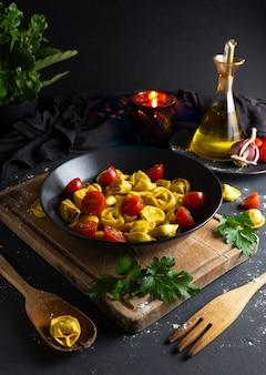 Ravioli mit tomaten auf schwarzblech in der rustikalen selbst gemachten lebensmittelumwelt, vogelperspektive
