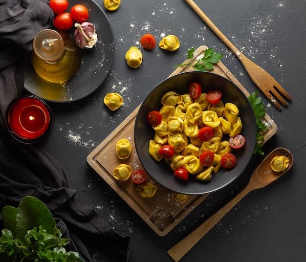 Ravioli mit tomaten auf schwarzblech in der rustikalen selbst gemachten lebensmittelumwelt