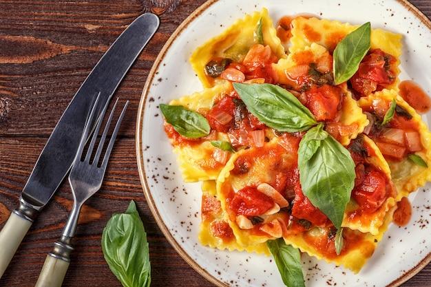 Ravioli mit tomatensauce und basilikum im dunkeln