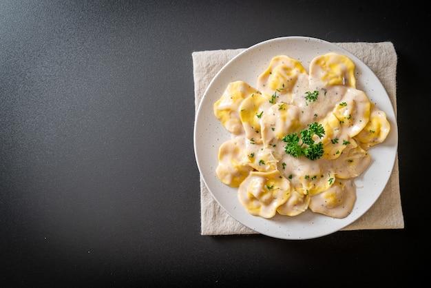 Ravioli-nudeln mit champignon-sahne-sauce und käse - italienische küche
