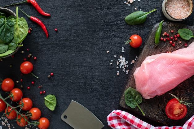 Raw putenfilet bereit zum grillen. hühnerfilet auf einem hölzernen schneidebrett mit kirschtomaten, peperoni, spinatblättern und grüns. kopieren sie platz. ansicht von oben