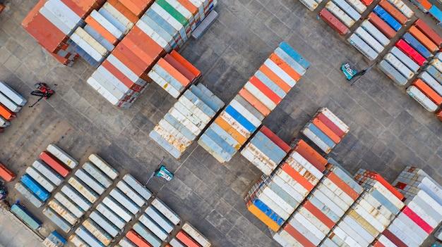 Reach stacker mit luftbildern bewegen container an einem frachtterminal, einem industriecontainerterminal und einem lagerbehälterbereich.