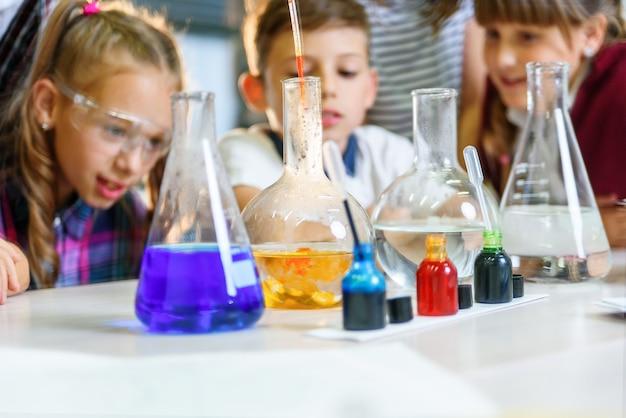 Reagenzgläser mit bunten flüssigen substanzen. untersuchung flüssiger zustände. gruppenschüler mit reagenzgläsern studieren chemische flüssigkeiten. wissenschaftskonzept. mädchen und jungen experimentieren mit flüssigkeiten.