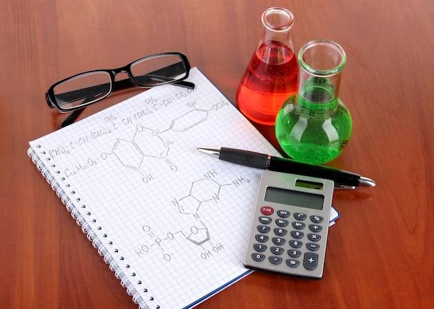 Reagenzgläser mit bunten flüssigkeiten und formeln auf dem tisch
