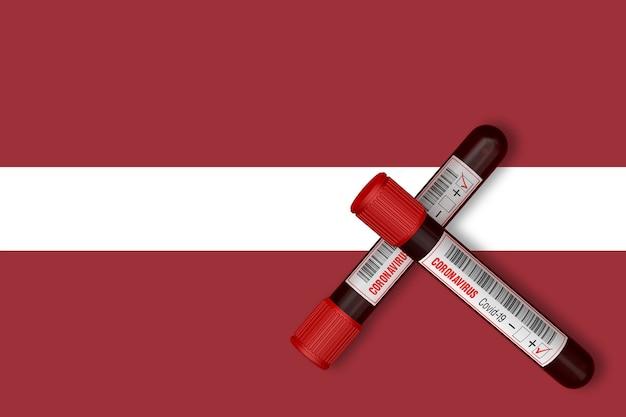 Reagenzgläser mit der aufschrift 2019-ncov auf dem hintergrund der lettischen flagge. 3d-rendering