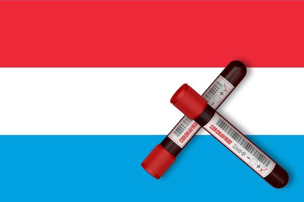 Reagenzgläser mit der aufschrift 2019-ncov auf dem hintergrund der luxemburger flagge. 3d-rendering