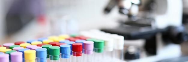 Reagenzglas mit farbigen kappen neben dem mikroskop. schnelltest auf coronavirus. technologie zur durchführung von experimenten. bluttest auf infektion. hygieneversuche werden in vitro durchgeführt