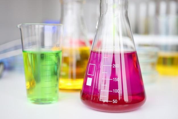 Reagenzglas mit roter flüssigkeit auf chemielabortisch-nahaufnahmehintergrund.