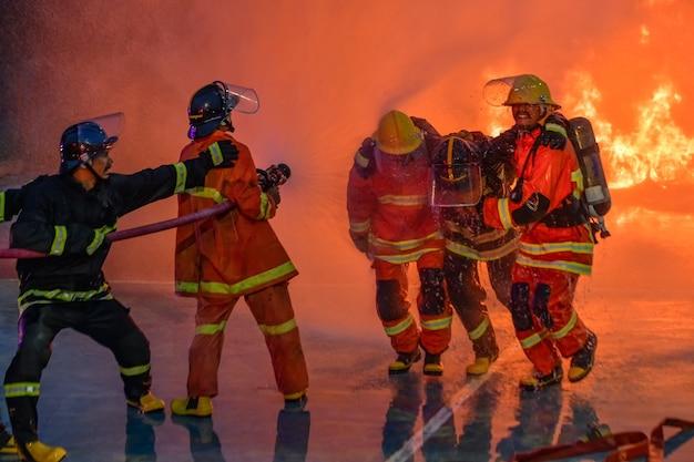 Realistische ausbildung von feuerwehrleuten, die feuer löschen und opfern helfenbrandschutzkonzept