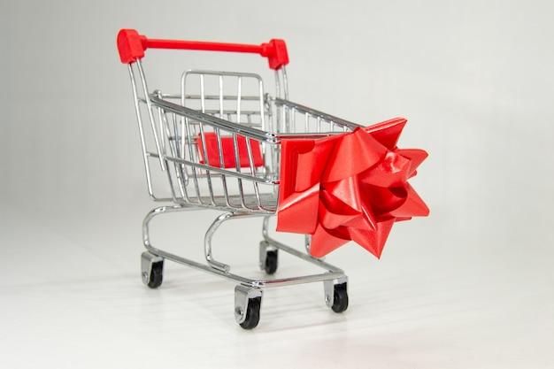 Realistischer eisen-mini-einkaufswagen mit kunststoffteilen mit roter weihnachtsschleife.