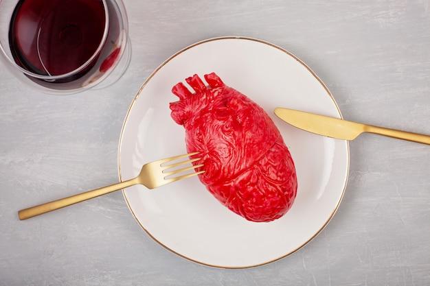 Realistisches herz auf dem speisetisch in der platte