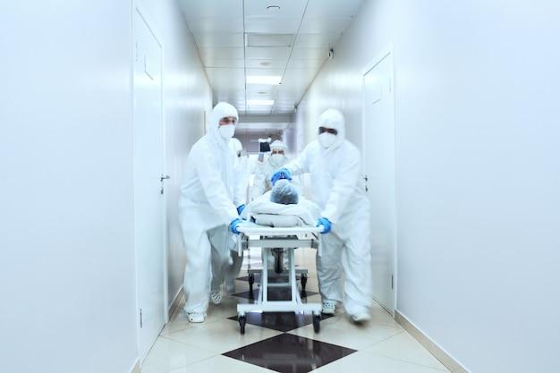 Reanimationsteam von ärzten, die patienten in sauerstoffmaske tragen, die auf einer bahre im krankenhaus liegen