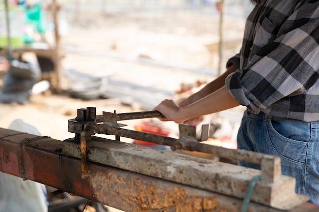 Rebar, der durch arbeitskraft auf rostiger spannvorrichtung in der baustelle verbiegt