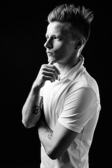 Rebellischer mann als punkrocker gegen schwarz in schwarz und weiß