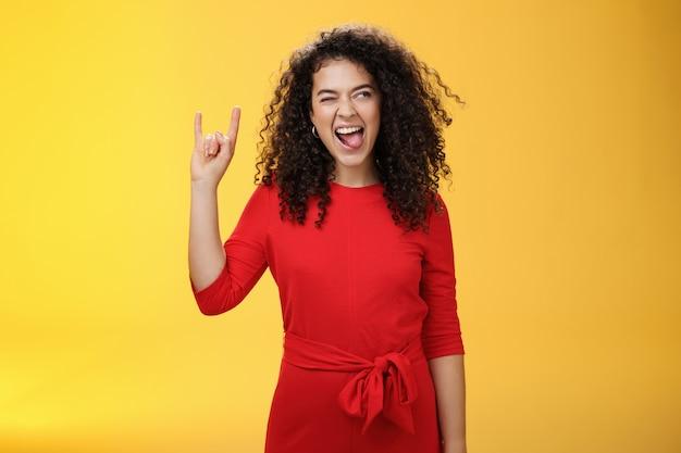 Rebellischer meloman, der im zarten mädchen geht. begeisterte und sorglose lockige frau in rotem kleid, die die zunge herausstreckt und mit einem lächeln nach rechts schaut, als sie rock-n-roll-geste zeigt und coole musik genießt.