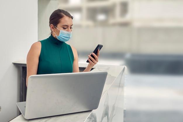 Recepcionista con cubrebocas wettbewerbando mensajes en su celular mientras trabaja