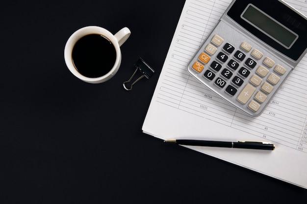 Rechner auf dokument mit tasse kaffee auf schwarzem tisch