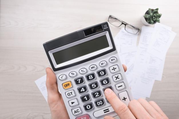 Rechnungen und taschenrechner mit schecks für waren und dienstleistungen. taschenrechner zur berechnung von rechnungen am tisch im büro. kostenberechnung.