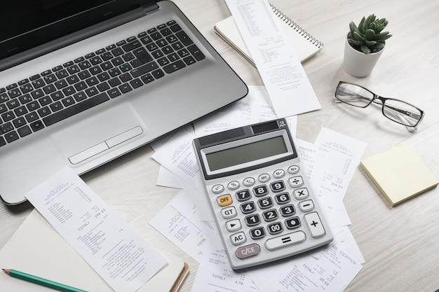 Rechnungen und taschenrechner mit schecks. taschenrechner zur berechnung von rechnungen am tisch im büro. kostenberechnung.