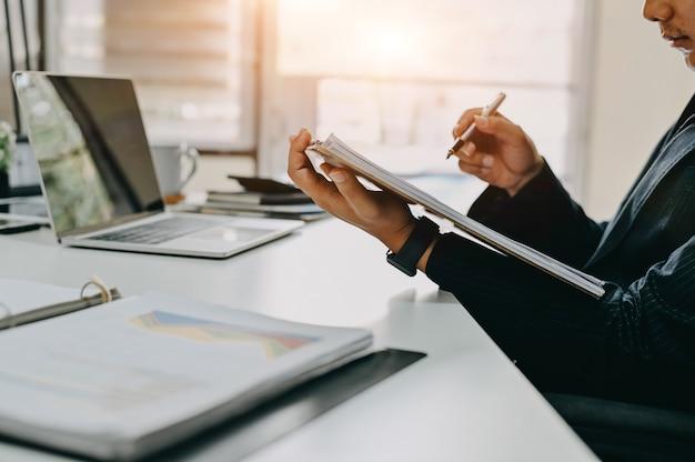 Rechnungsprüfungsfunktion, geschäftsmannarbeit mit papierdokument auf schneidebrett im büro.