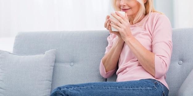 Recht ältere frau, die zu hause einen kaffee genießt