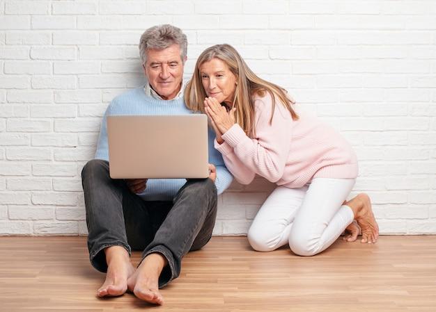 Recht ältere paare, die auf ihrem hausboden mit einem laptop sitzen