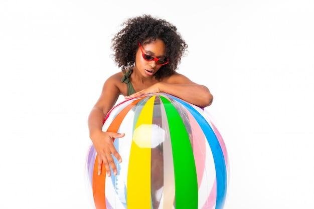 Recht afrikanische frau im badeanzug steht mit dem großen bunten lokalisierten gummiball