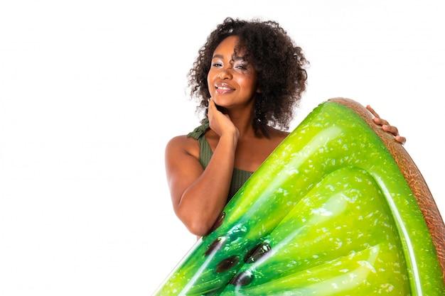 Recht afrikanische frau steht im badeanzug mit gummistrandkiwimatratze und lächelt lokalisiert