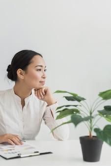 Recht asiatische frau, die an ihrem arbeitsplatz sitzt