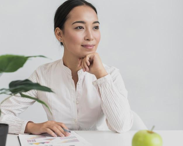 Recht asiatische frau, die in ihrem büro sitzt