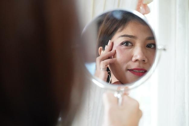 Recht asiatische frau, die spiegel nach der prüfung ihrer falte sucht