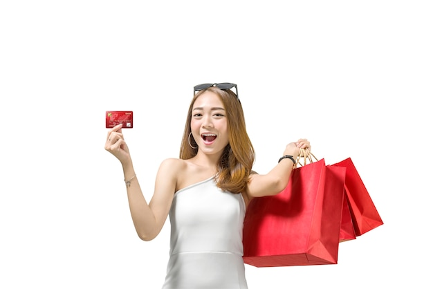 Recht asiatische frau mit den roten papiertüten, die ihre kreditkarte zeigen