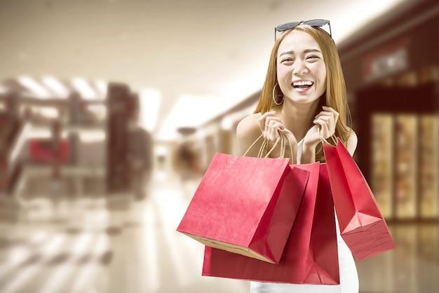 Recht asiatische frau mit roten papiertüten auf dem mall