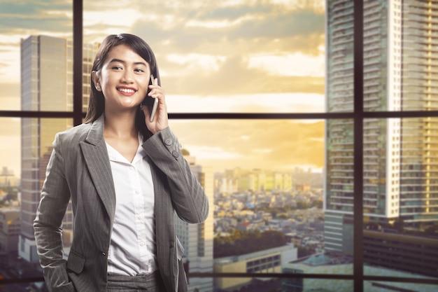 Recht asiatische geschäftsfrau, die auf smartphone spricht