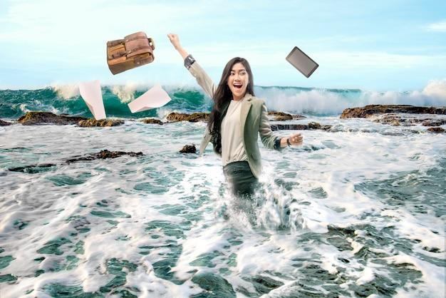 Recht asiatische geschäftsfrau, die ihr arbeitsgerät wirft und ferien auf dem strand macht