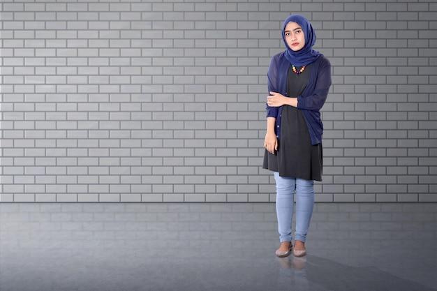Recht asiatische moslemische frau, die mit überzeugtem steht