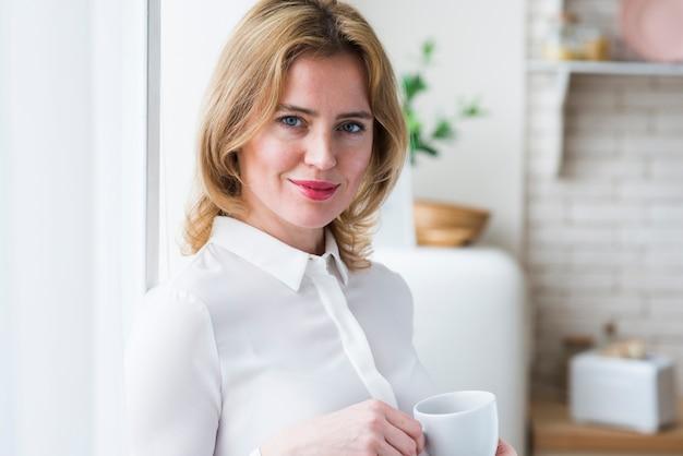 Recht blonde geschäftsfrau, die mit kaffeetasse steht