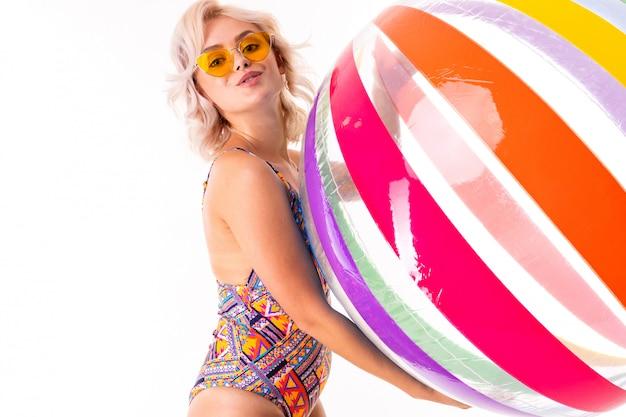 Recht blonde kaukasische frau steht im badeanzug mit dem bunten ball und lächeln des großen gummistrands, die lokalisiert werden