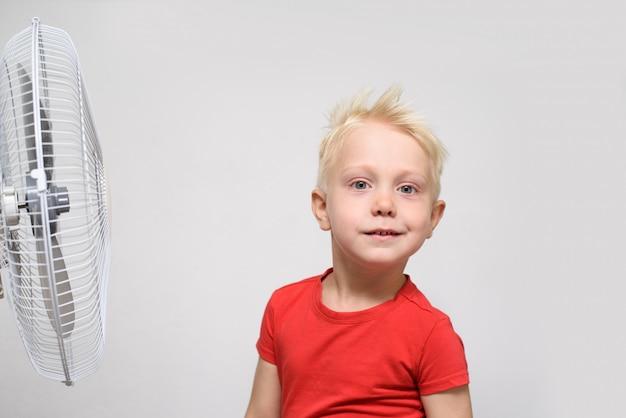 Recht blonder junge im roten hemd die kühle luft genießend. sommer-konzept.