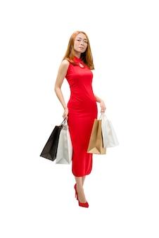 Recht chinesische frau mit dem cheongsam kleid, das einkaufstaschen hält