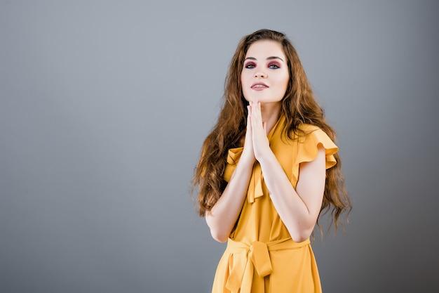 Recht emotionale frau, die lokalisiert über grauer wand hofft und betet