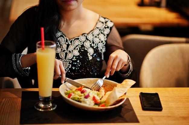 Recht indisches mädchen im schwarzen sareekleid warf am restaurant auf und saß bei tisch mit saft und salat.