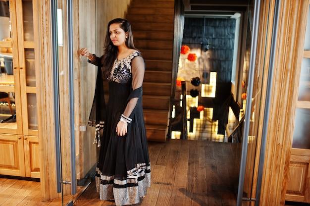 Recht indisches mädchen im schwarzen sareekleid warf am restaurant auf.