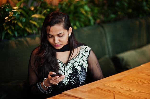 Recht indisches mädchen im schwarzen sareekleid warf am restaurant mit dem handy zur hand auf.