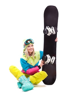 Recht junge blonde frau im bunten schneeanzug, der im schneidersitz sitzt