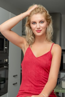 Recht junge blonde frau mit einem roten kleid zu hause
