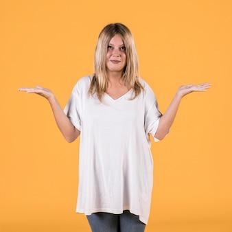 Recht junge blonde haarfrau, die schultern über gelbem hintergrund zuckt