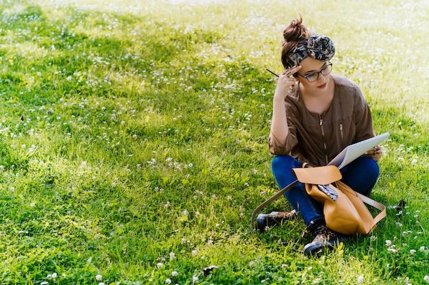 Recht junge frau, die auf dem gras sitzt und papiere liest