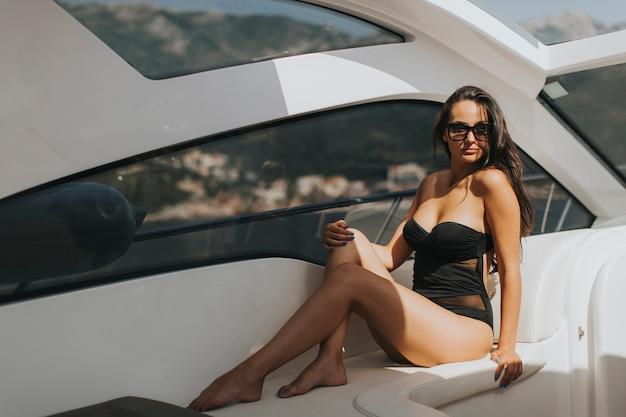 Recht junge frau, die auf der yacht am sonnigen tag sich entspannt
